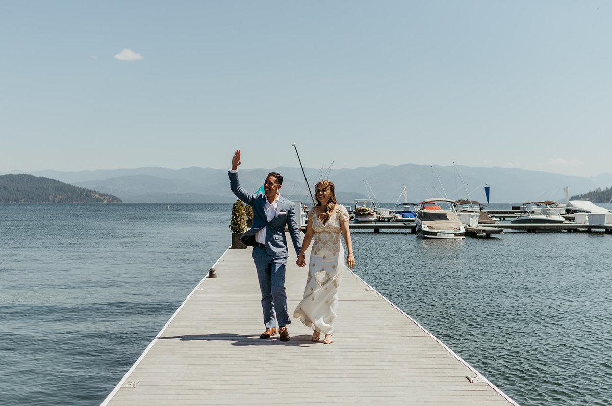 Couer d'Alene bride & groom waving from waterfront