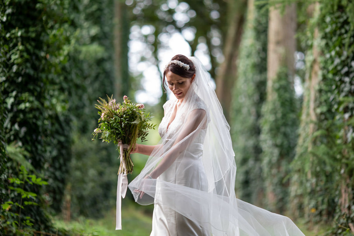 Bride between trees at Coombe Trenchard Devon