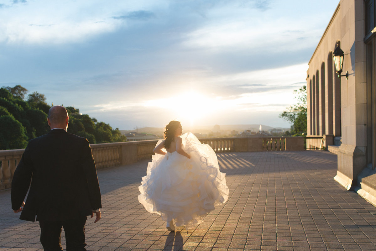 Bride and groom walking into the sunset on Chateau Laurier terrace