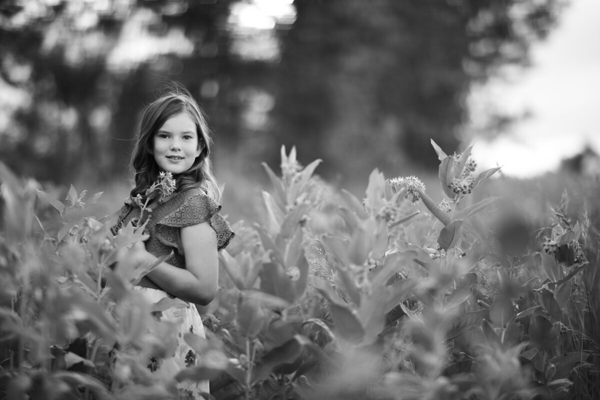 black and white photo of girl in milkweed flowers, holding a flower near sunset at joels pond in billings montana behind scheeles sporting goods store.