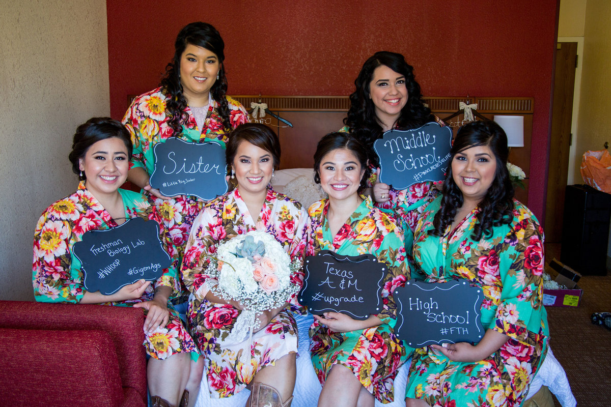 Bride and Bridesmaids holding prop signs during getting ready for wedding ceremony at Mission Concepcion