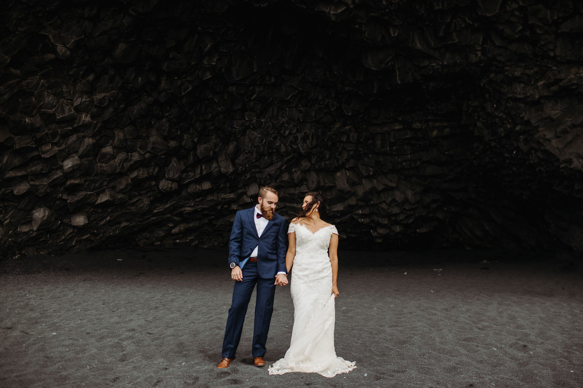 Bride & groom pose as the winds at Vik Beach blow their hair across their face after their Iceland wedding.