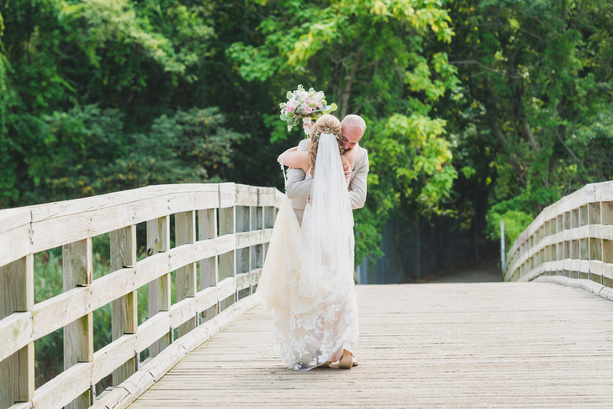 photo of bride and groom hugging on the bridge from wedding at Pavilion at Sunken Meadow