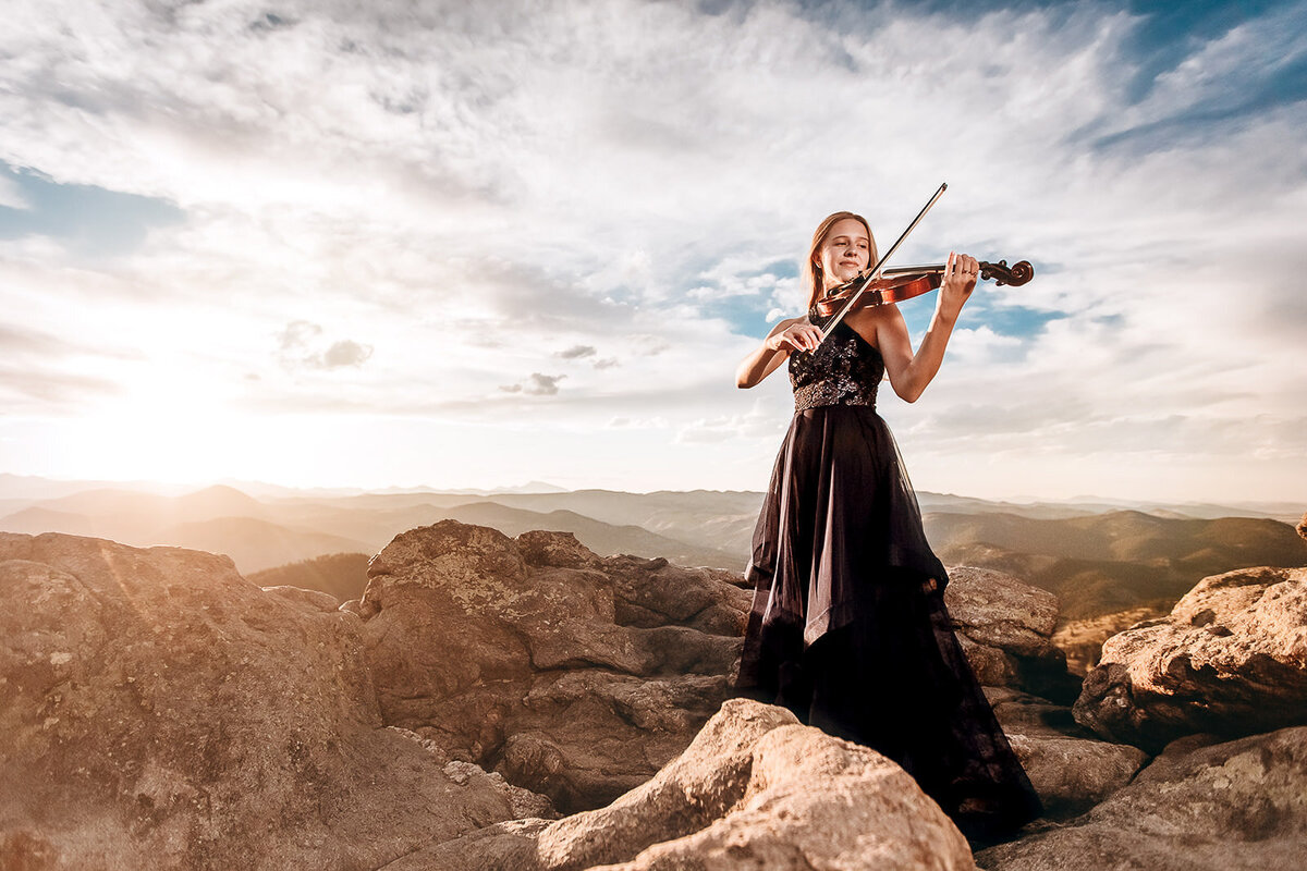girl with violin on a mountain top at sunset