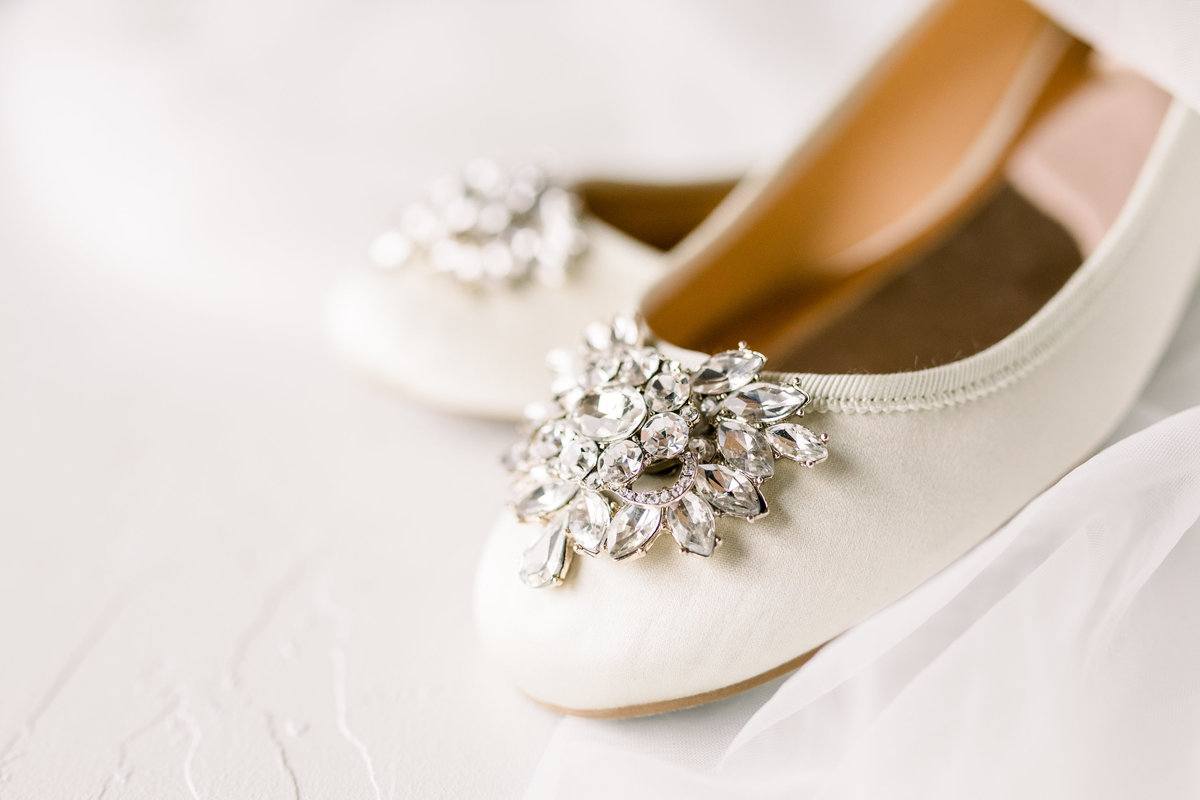 Close up detail of a bride's shoe. White flats with a jewel on the front