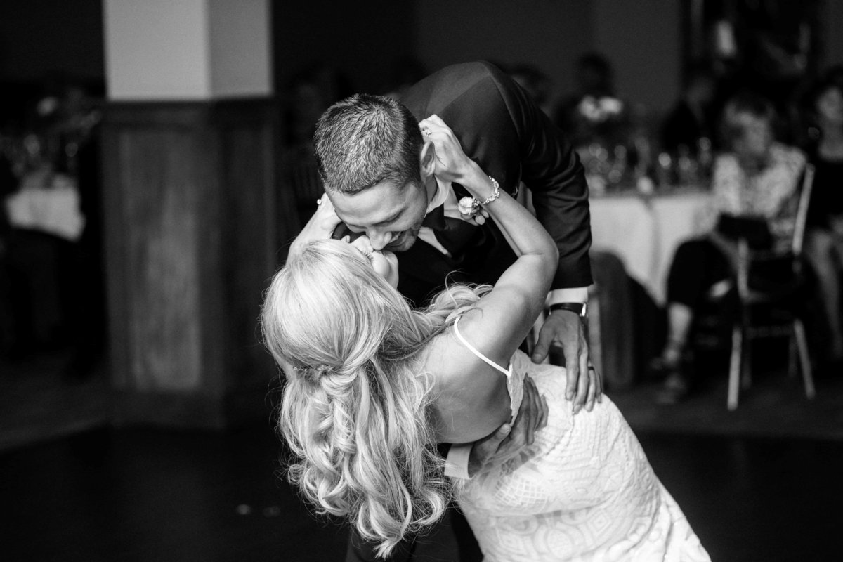 Black and white photo of a bride and groom dipping at the end of their first dance