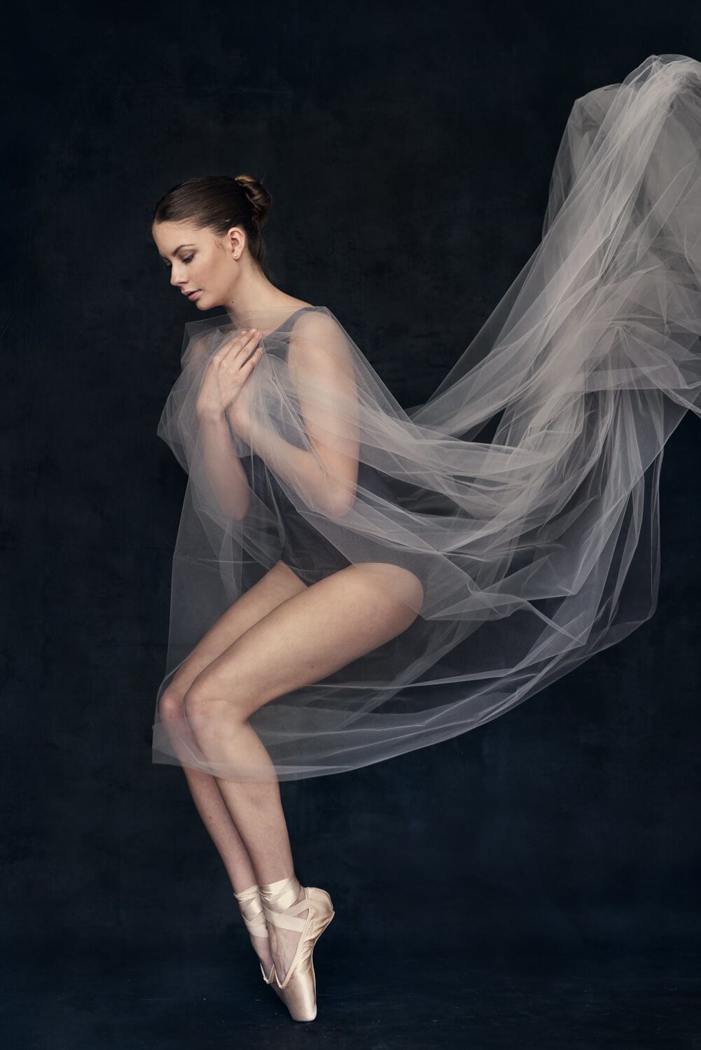 Briana on her pointe shoes dancing with a tulle fabrice flying behind her