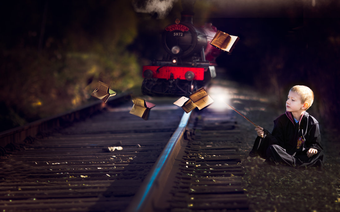 Boy sitting by train tracks with magic books flying