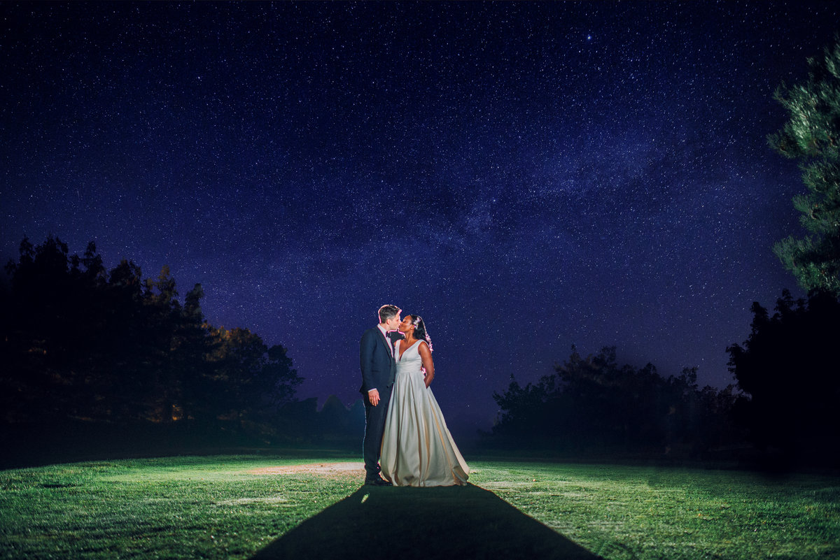 bride and groom kiss beneath a starry sky