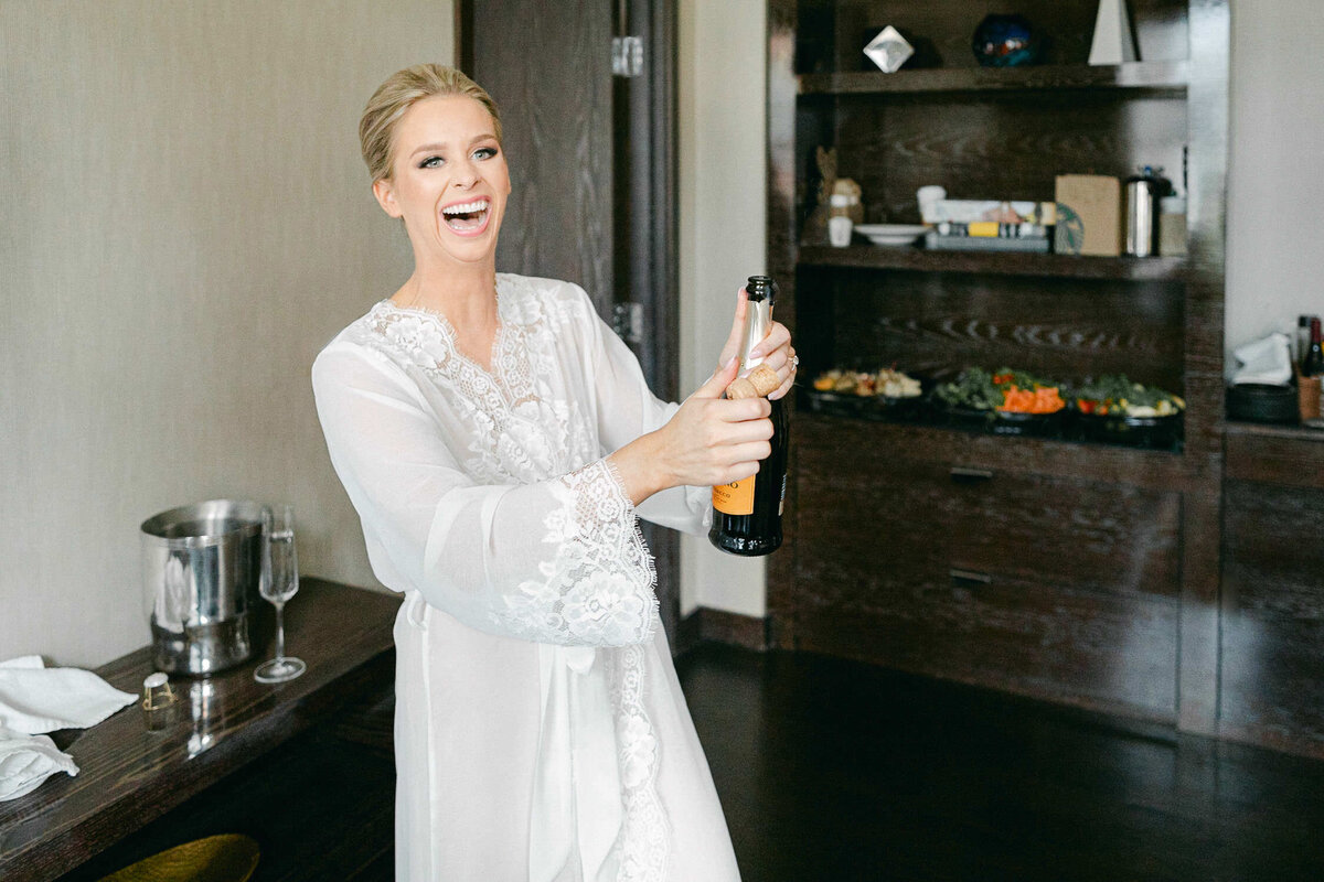 woman in white robe laughing and popping champagne bottle