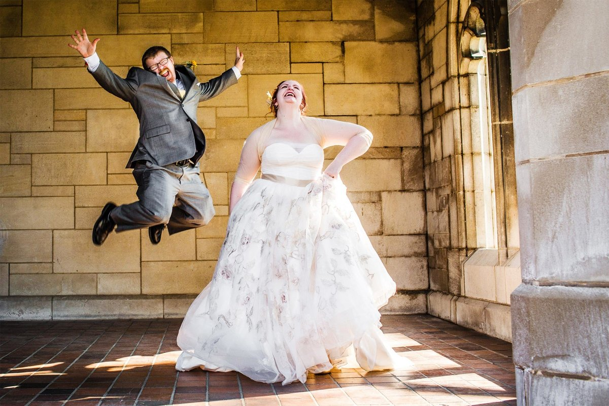 A groom jumps in the air with joy during a University of Chicago wedding.