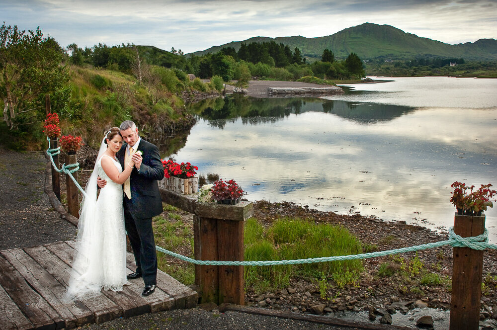 bride wearing an a-line style wedding dress with scooped back embracing her grey haired groom while standing on a wooden bridge overlooking Golden Cove, Sneem