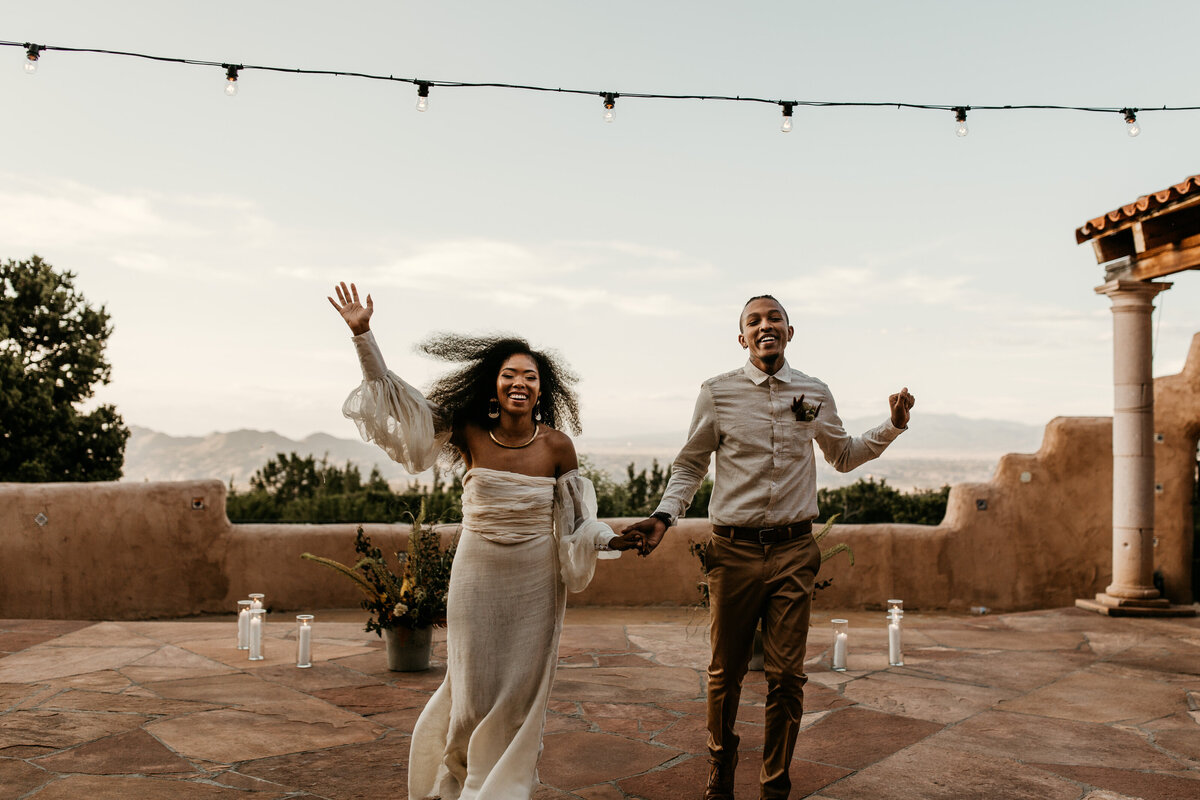 bride and groom running and cheering in courtyard venue