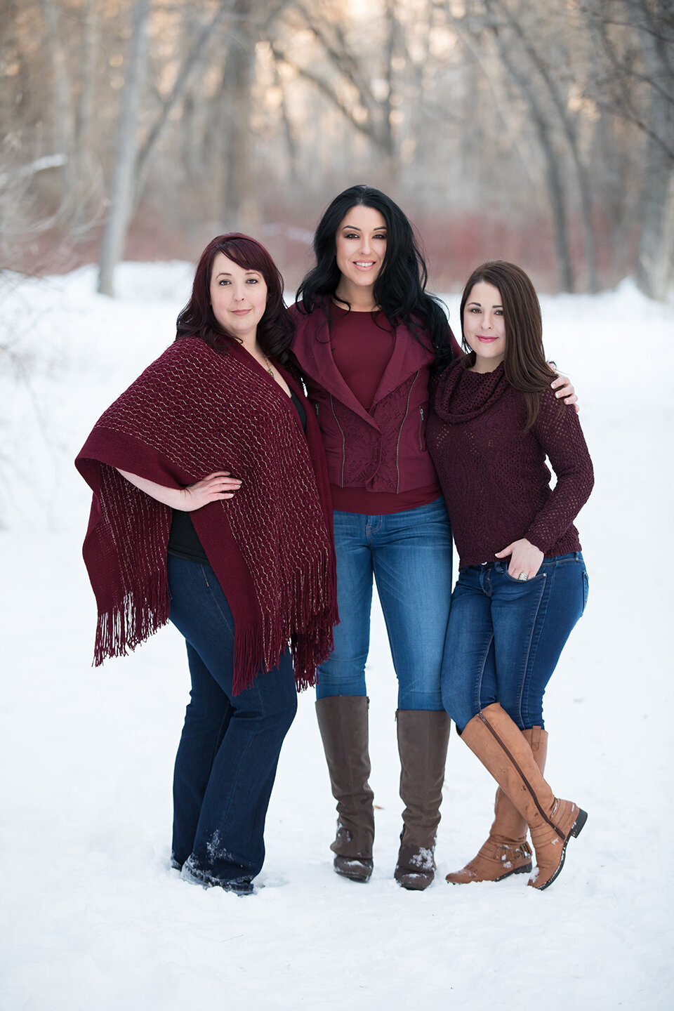 three sisters in maroon shirts, blue jeans and boots  in the snow, located at river front park in the winter. family pictures photographed in billings mt