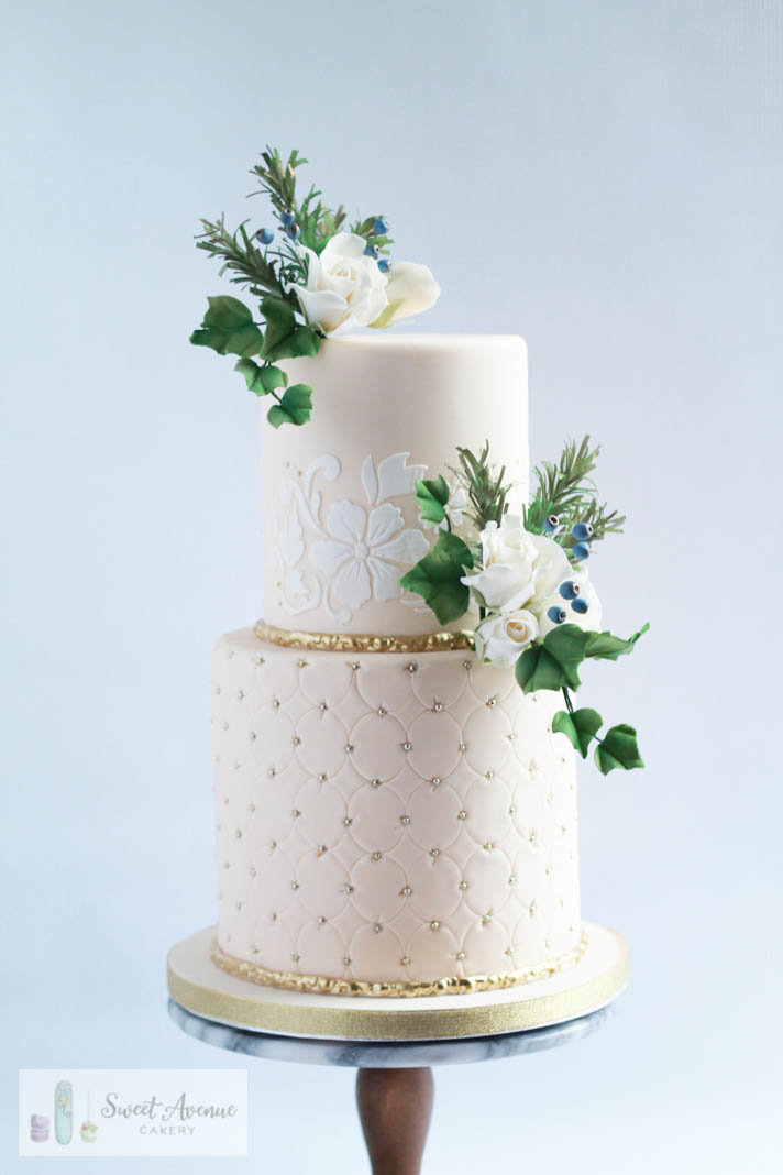 winter wedding cake with lace and evergreens