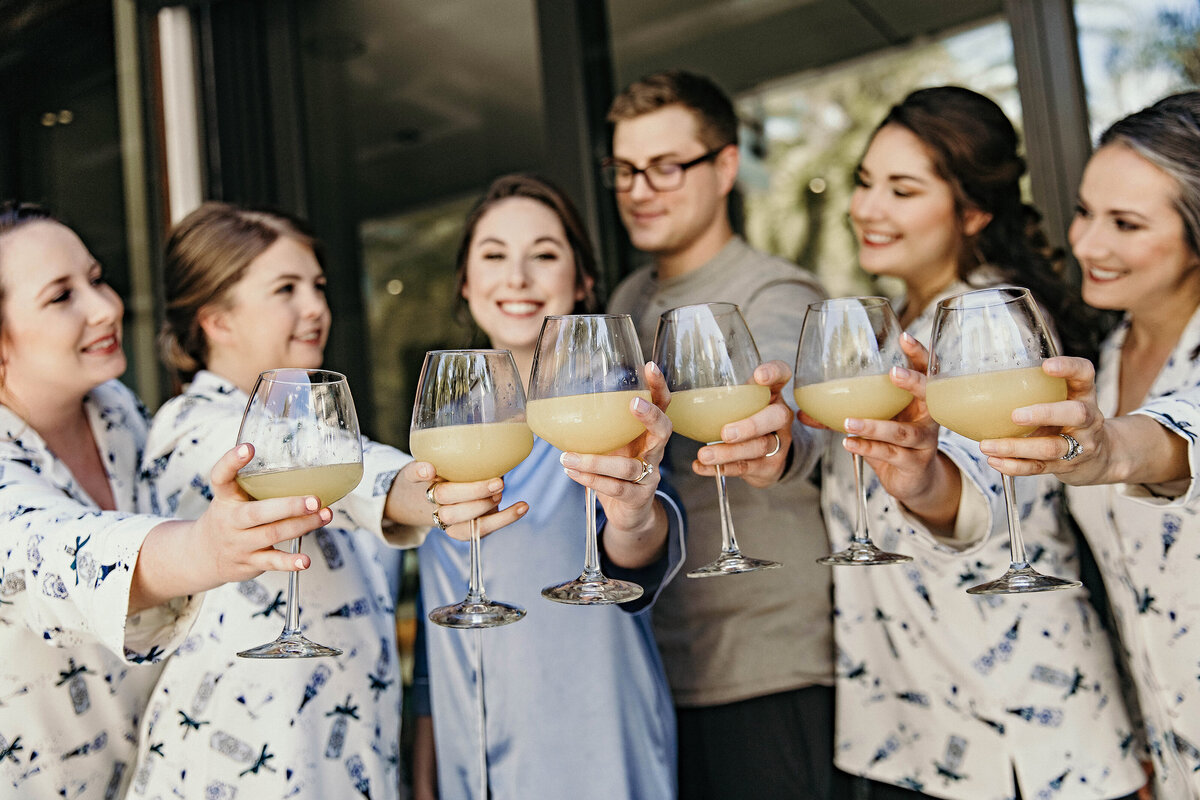 A photograph of the bride and her bridesmaids and friend, relaxing together before the wedding in their short matching robes as they each hold up their glass of champagne by Garry & Stacy Photography Co - Tampa wedding photography and videography
