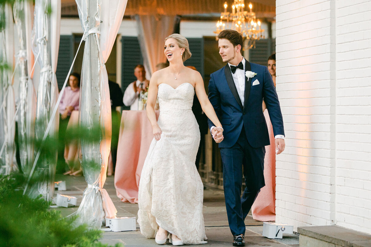 bride and groom laughing holding hands walking into wedding reception Dallas Arboretum
