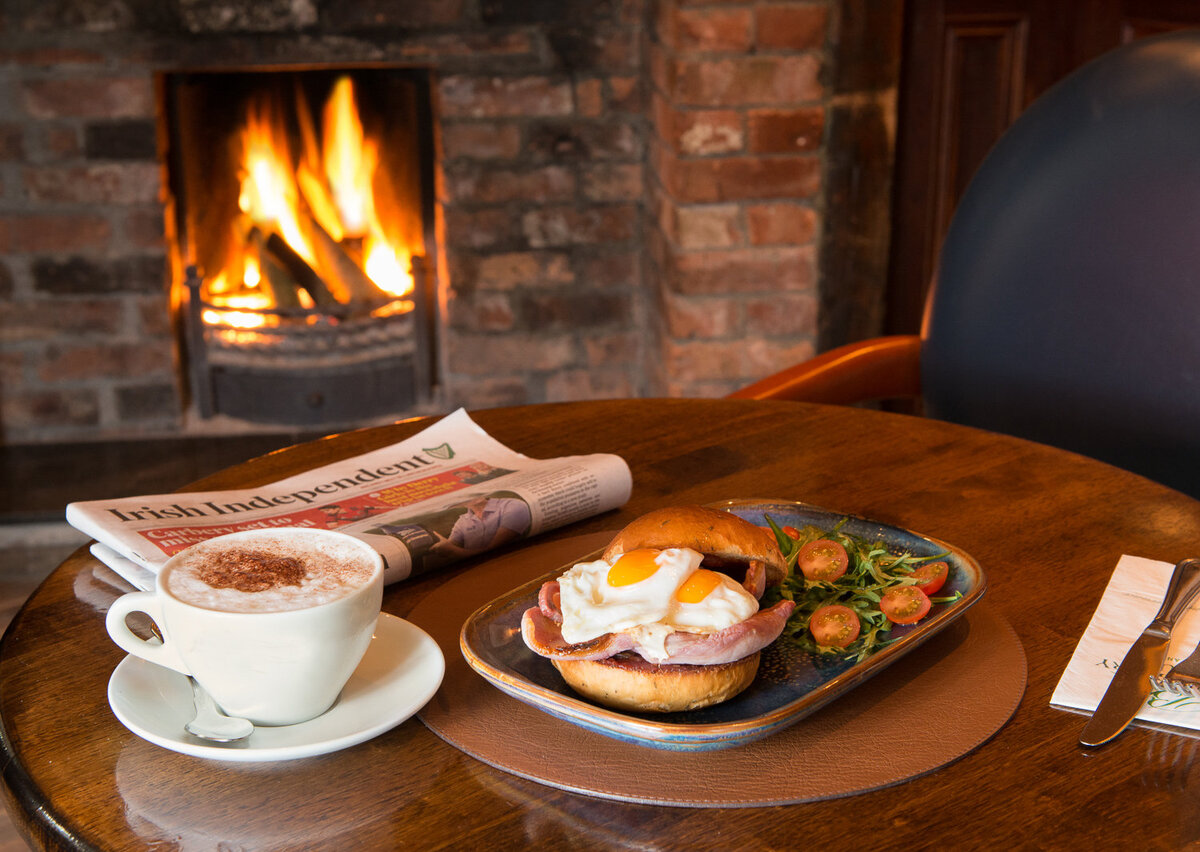 Egg and bacon bap with coffee by the fire