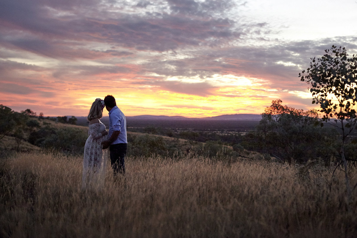 Pregnant wife and husband embracing and looking at the sunset in natural bushland