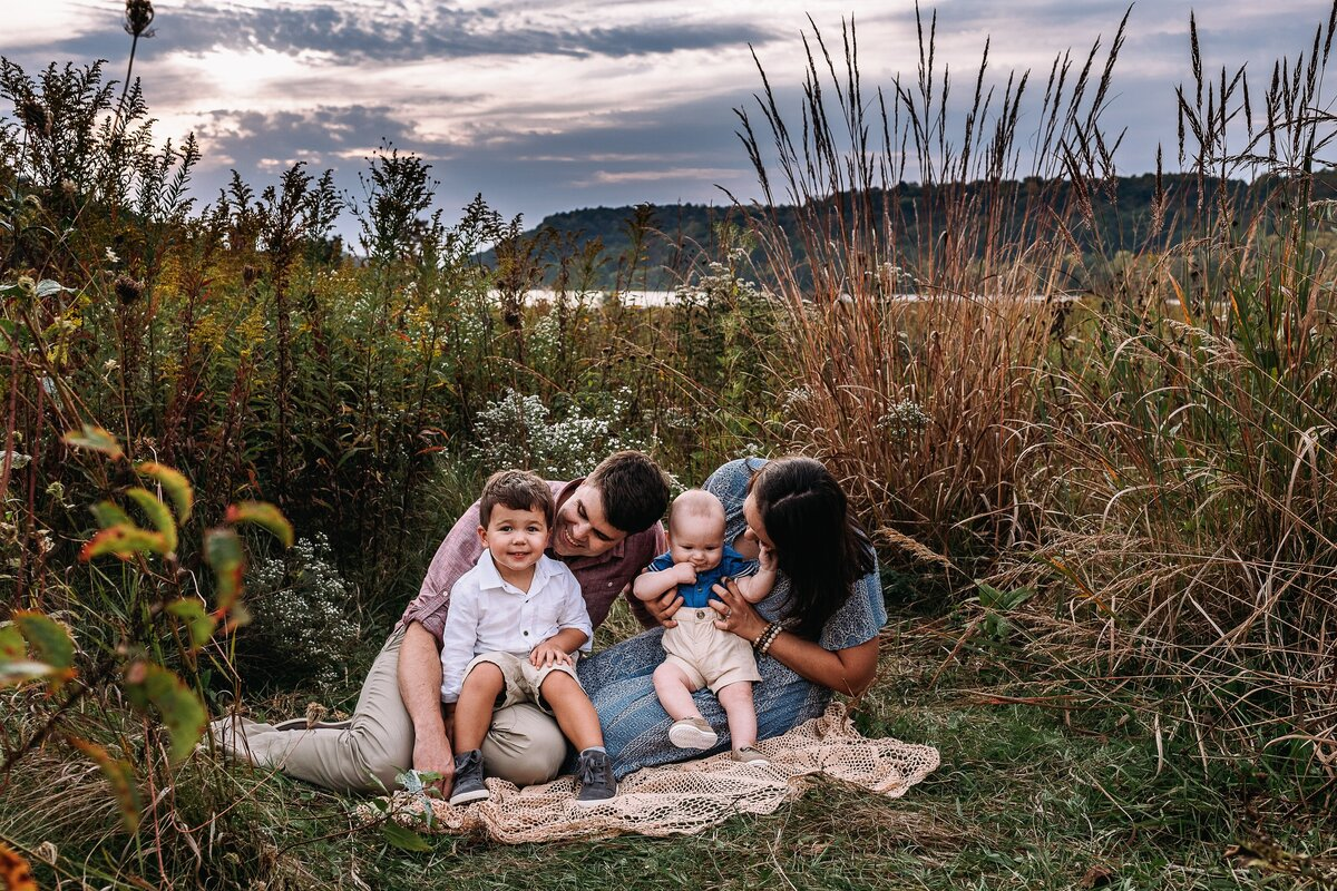 Parents sitting on lace blanket holding toddler and baby in a tall field of grass and flowers, sunset and lake behind them.