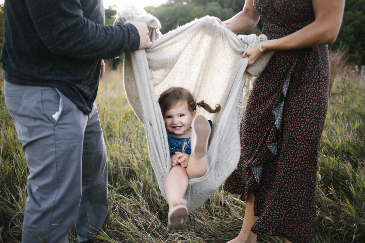 Mom and dad carrying little girl in a blanket during sunset session with Elle Baker Photography