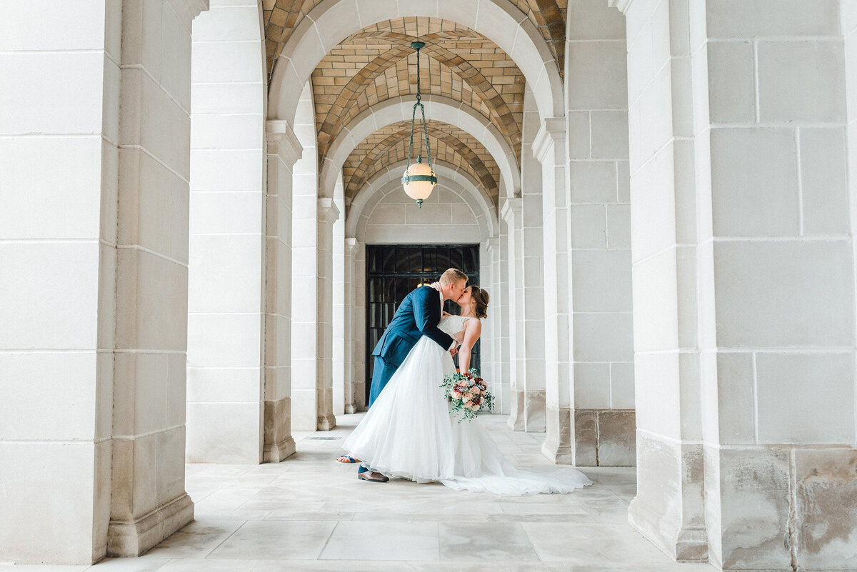 a groom dips and kisses his bride at Nebraska state capital building