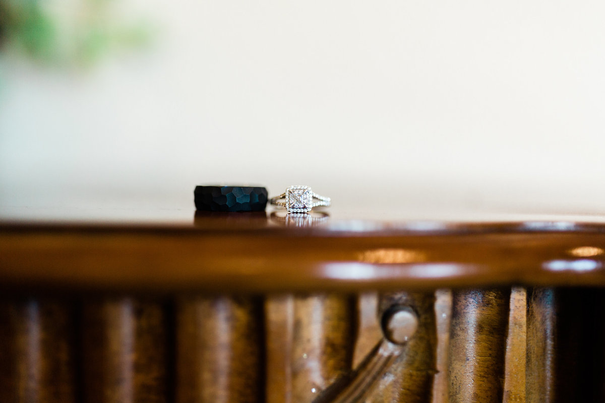 black mens wedding ring and halo cushion diamond wedding ring sitting together on a wooden table