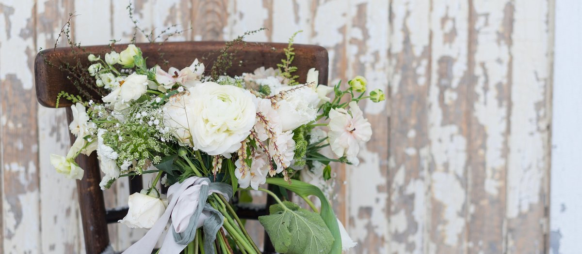 White and Green bridal bouquet sitting on dark wood chair in front of barn door photo