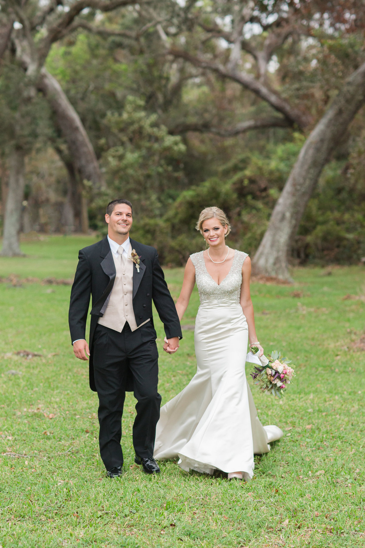 bride and groom walking and smiling  at their Jekyll Island Wedding