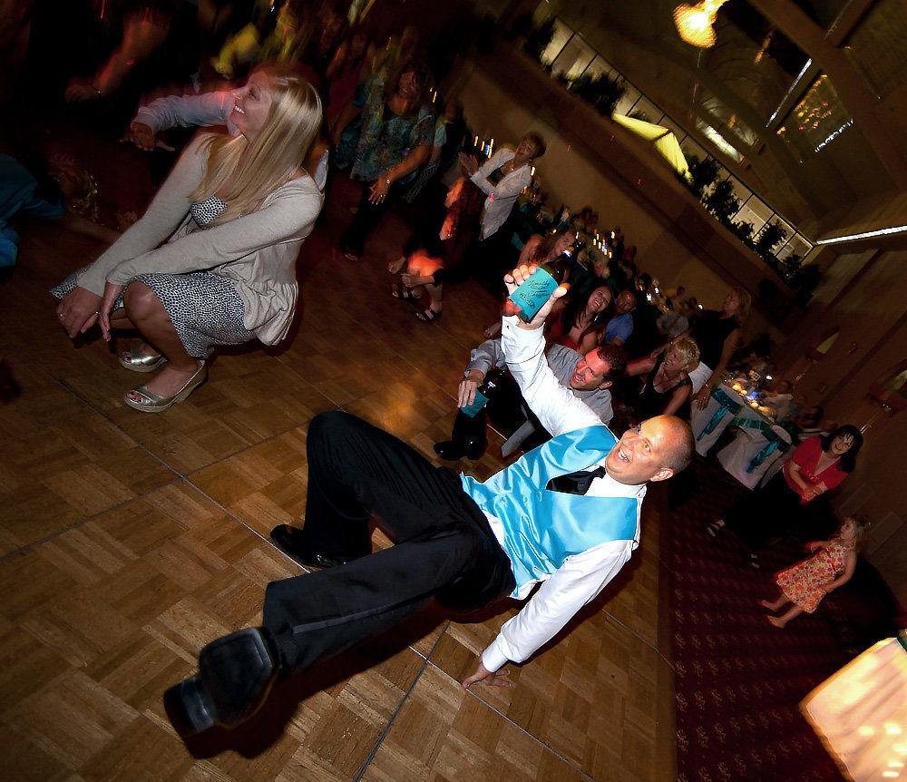 Groomsman balances beverages and wild dancing during the reception