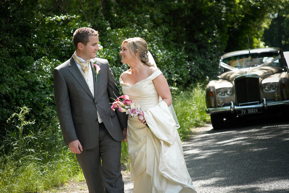 blonde bride in ivory silk walking with groom wearing a grey suit on a tree-lined country road with a vintage Rolls Royce car in the background