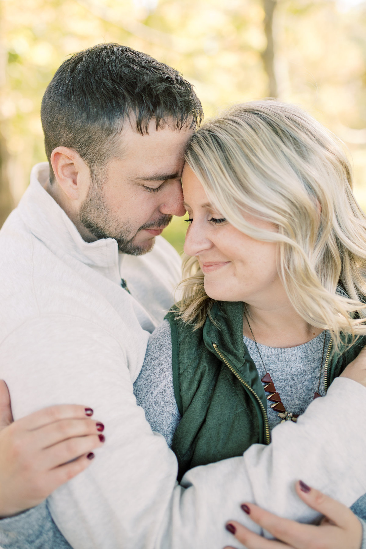 A couple embraces with their eyes closed during their engagement session