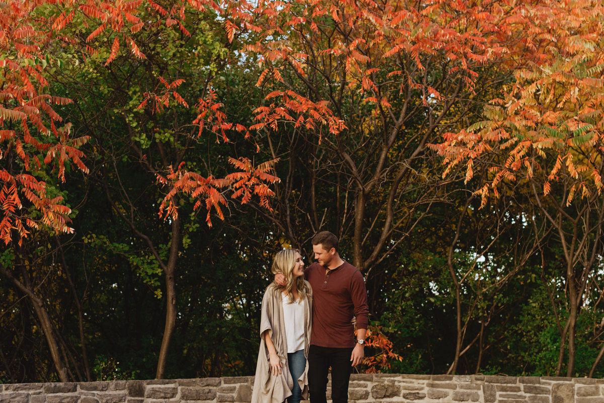engaged couple walking in the fall trees