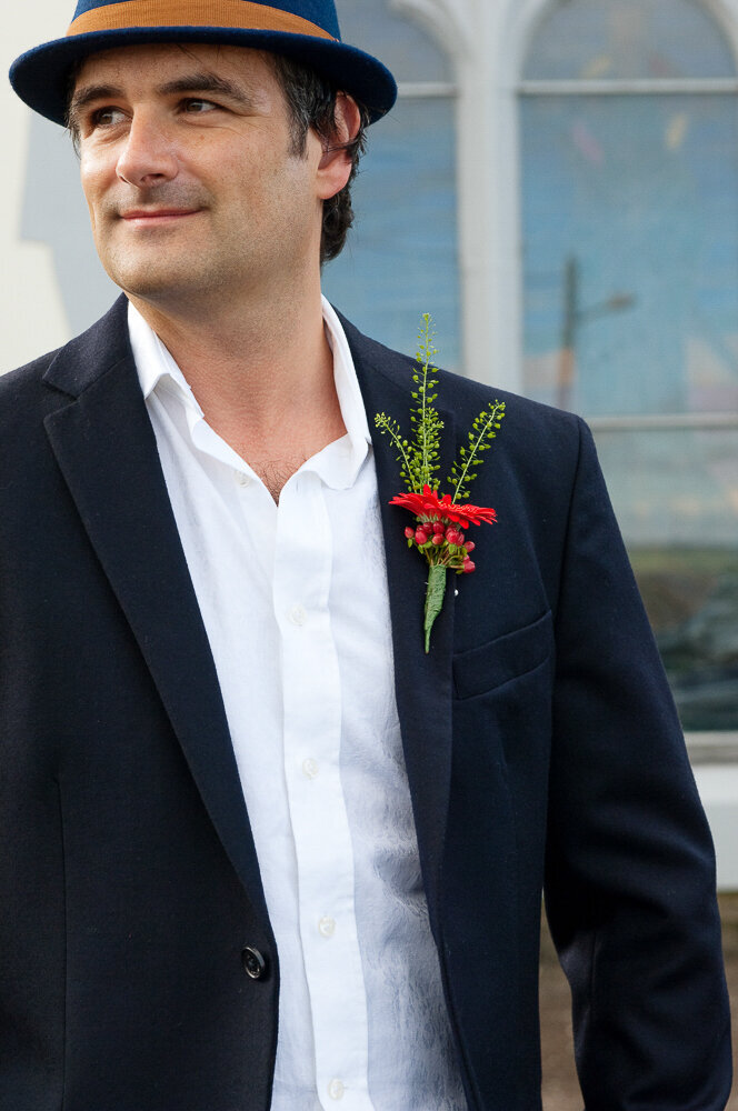groom wearing a dark navy wedding suit and red buttonhole flower with a navy trilby hat with tan band