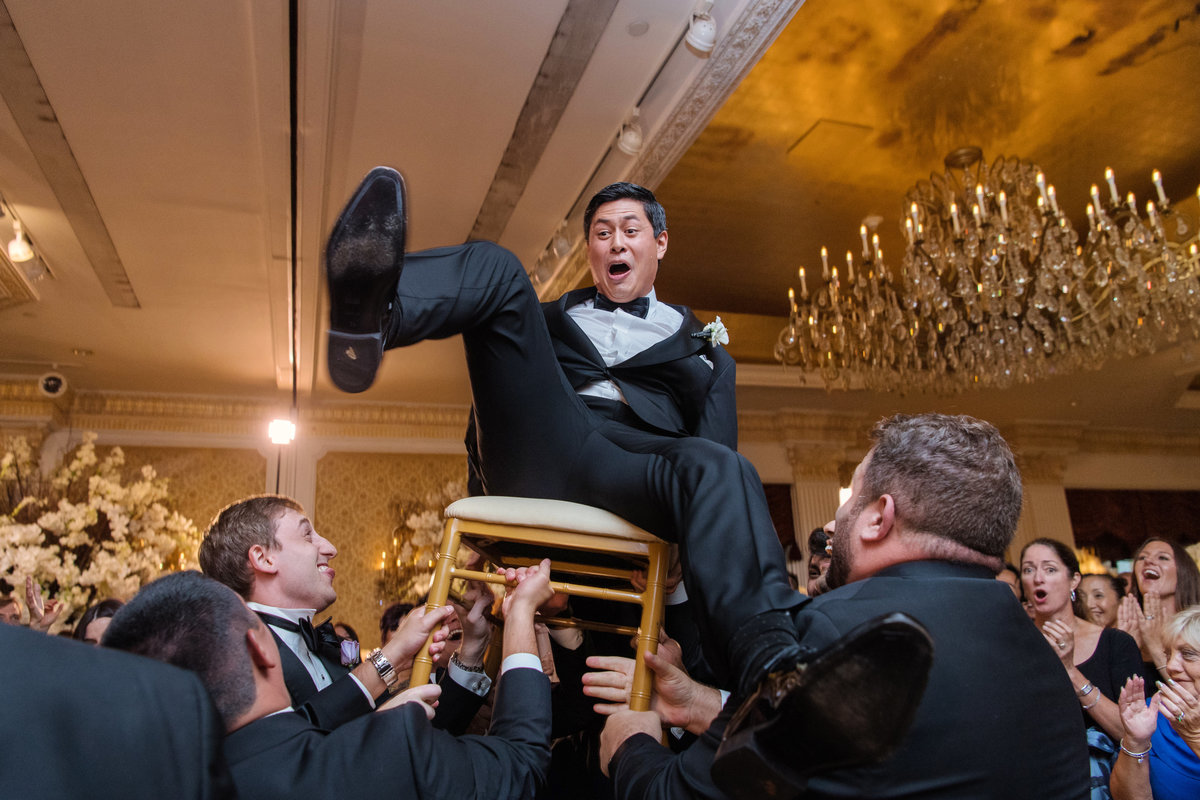 photo of groom during the chair dance during wedding reception at The Garden City Hotel