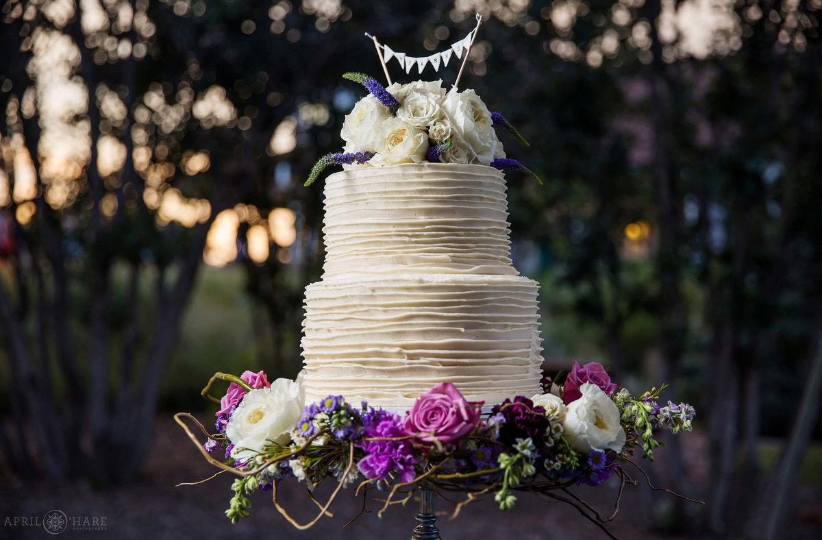 Stunning photo of a white wedding cake at sunset Chatfield Farms in Colorado