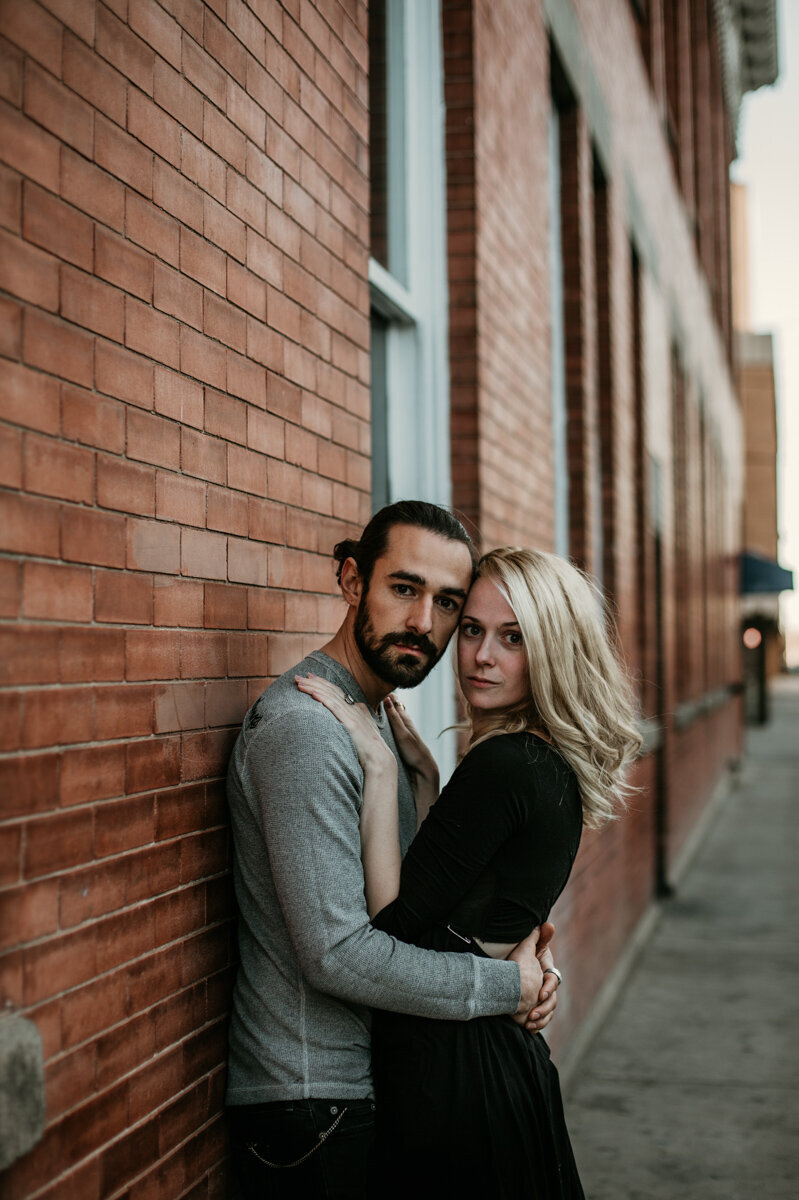 couple leaning against brick wall downtown Albuquerque