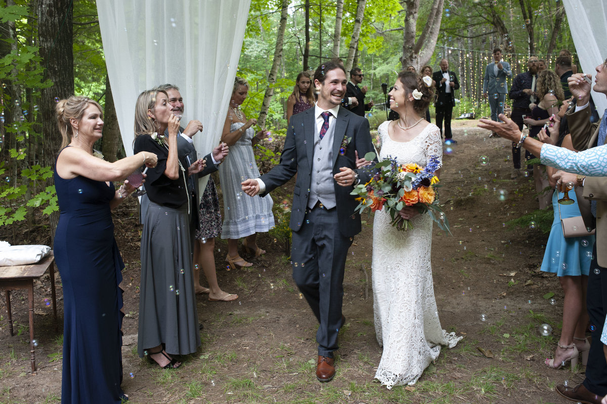 Bride & groom smiling at each other while walking through bubbles blown by wedding guestsat wedding in Otisfield, Maine