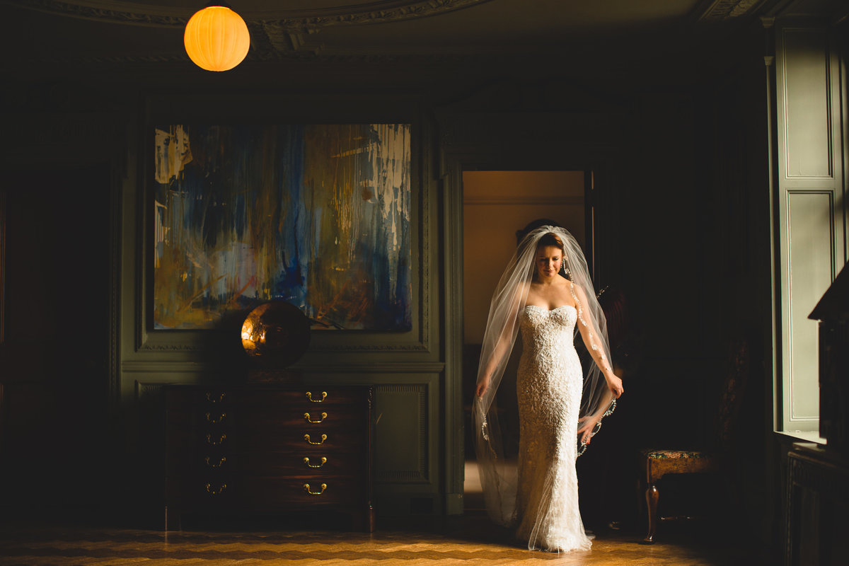 bride holding her veil as she walks at thornton manor lit by window light