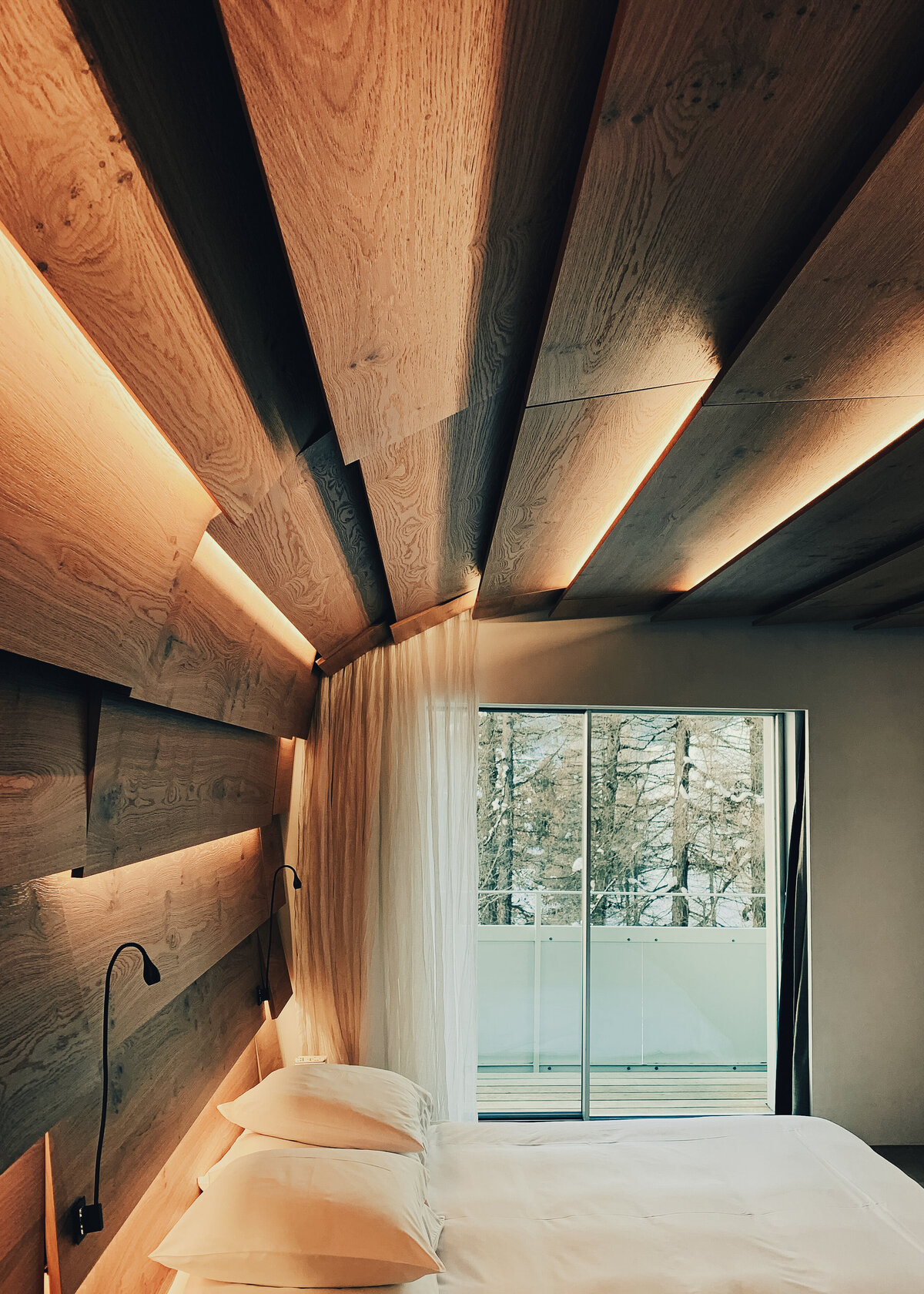 A ceiling is clad with natural oak with warm golden lighting in between with a white bed underneath.