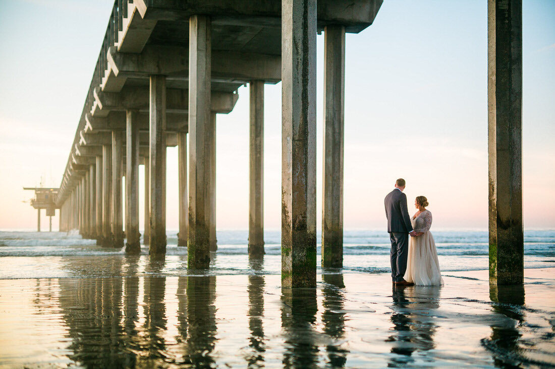 Bride & Groom embrace under a pier on the beach after their Scripps by the Sea wedding ceremony.