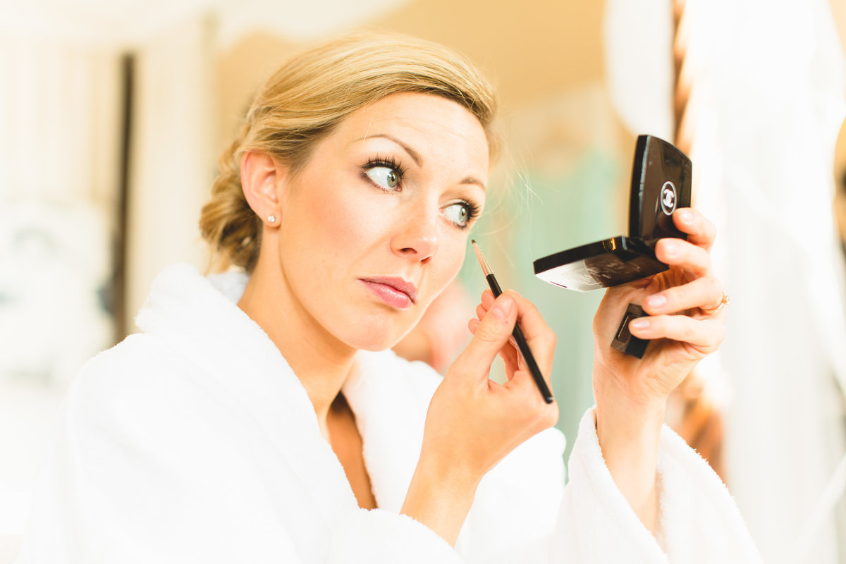 bright photo of bride doing her own makeup