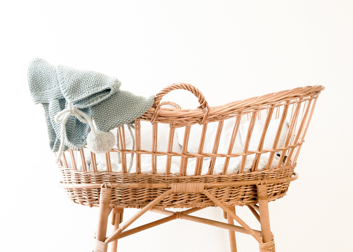 A rattan cradle is against a white wall with a blue baby bonnet over the side.