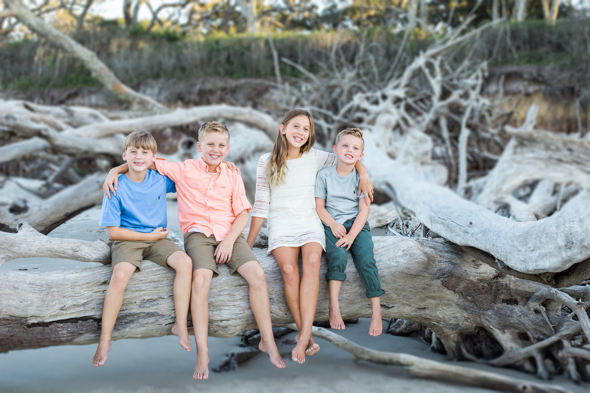 Family portrait of four school aged siblings taken at big talbot island by Jacksonville Family Photographer