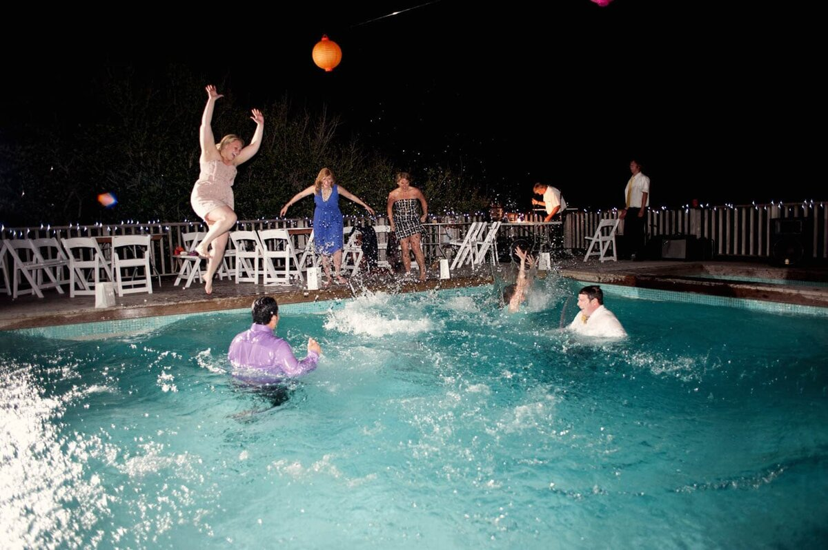 wedding guests jump in a pool after the wedding