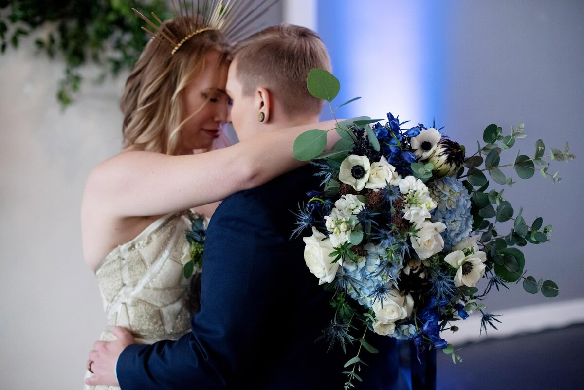 a same sex couple hugs while holding a pretty blue and white bouquet by flowers by alana