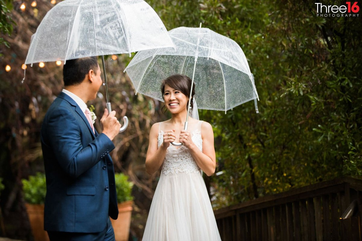 Newly married couple gaze upon each other during a rainfall