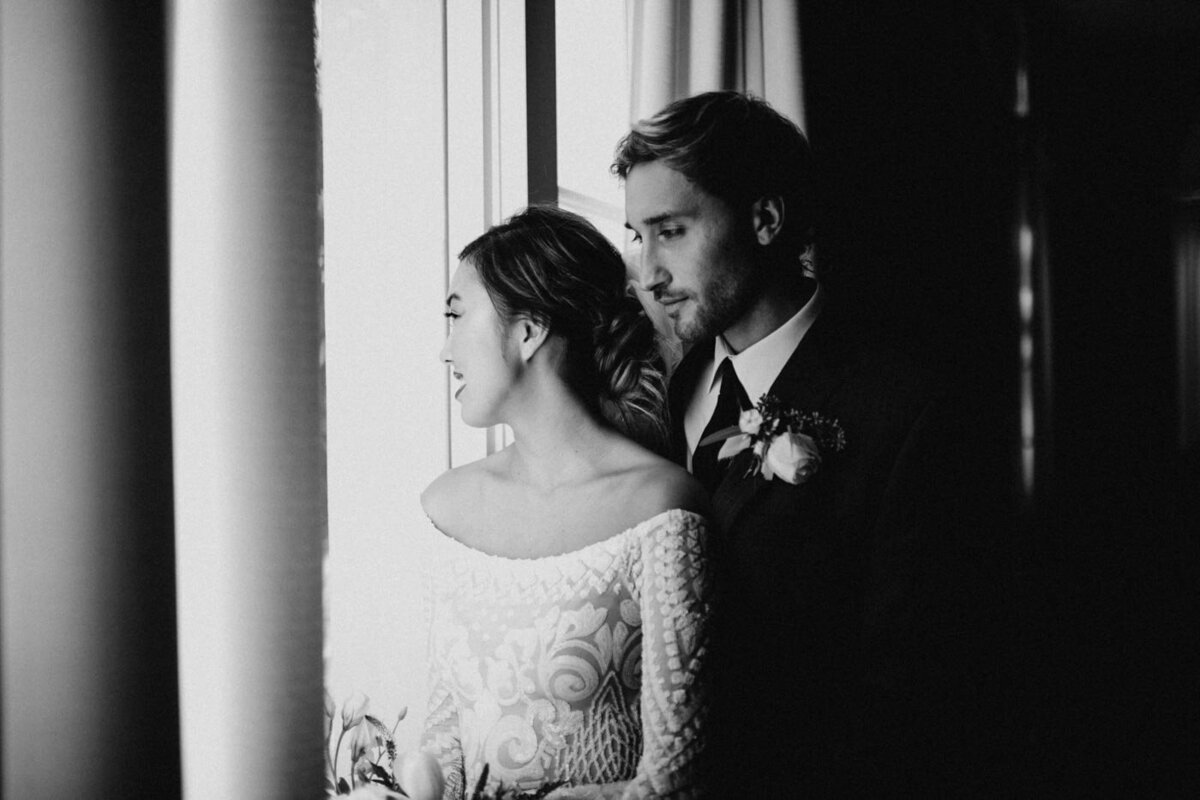 Groom-holds-bride-around-the-waist-as-they-look-out-the-window