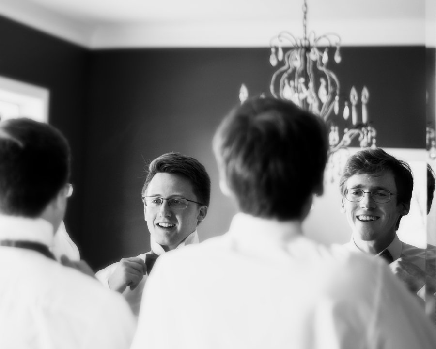 Black and White of Groom and Groomsman tying Bow Ties