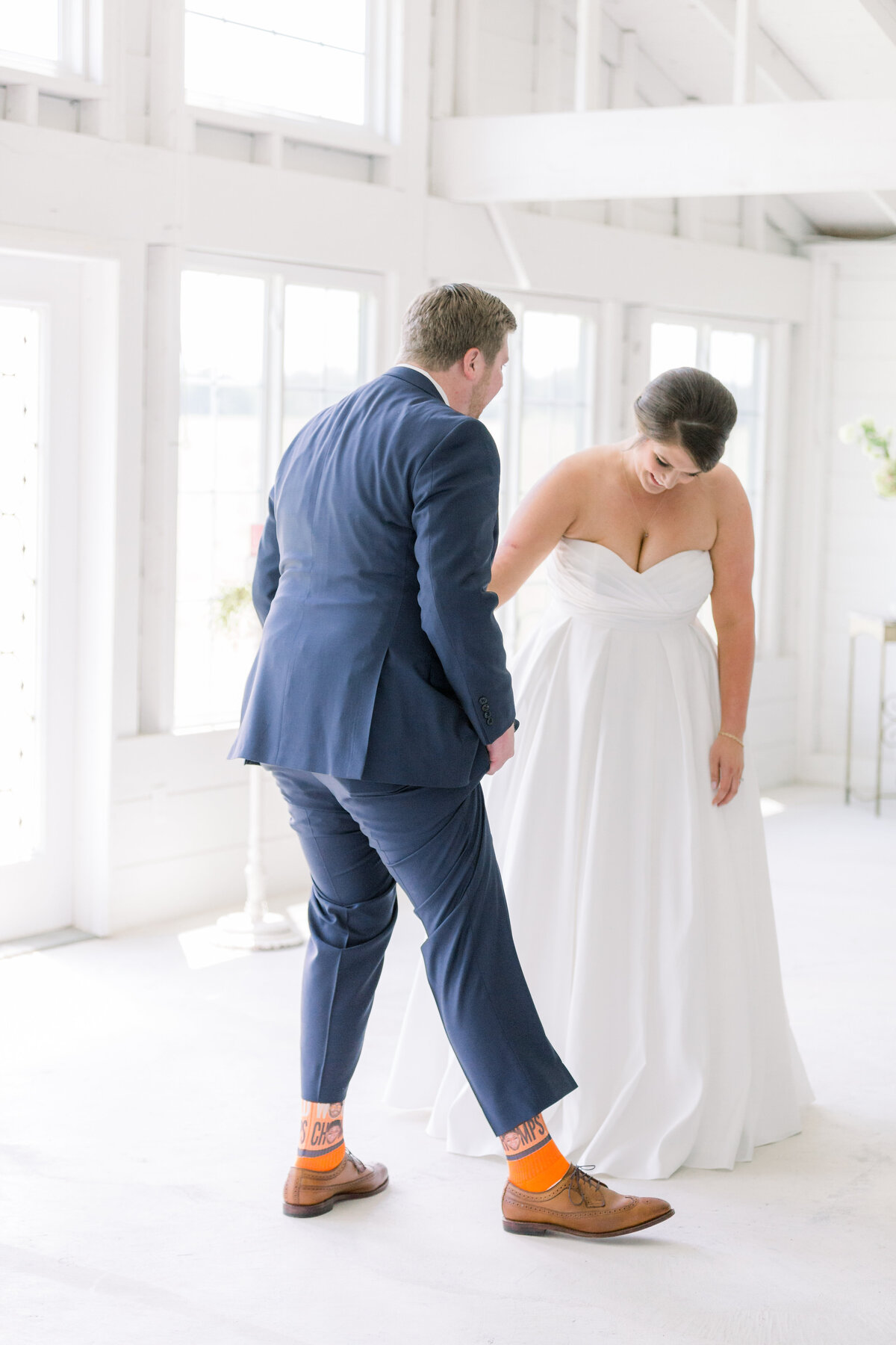 A bride and groom first look on wedding day. The groom is showing the bride his shoes and socks he bought for wedding day